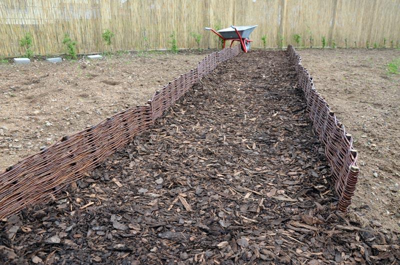 gemulchter Gartenweg zu den Clematis mit Weide-Beeteinfassungen