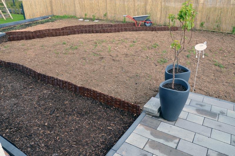 Terrassenblick auf Gartenwege mit Weidenbegrenzung